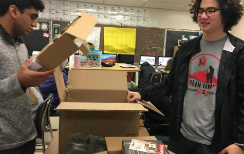 Seniors Manit Patel and Austin Aldrich open up the package containing the podcasting equipment.