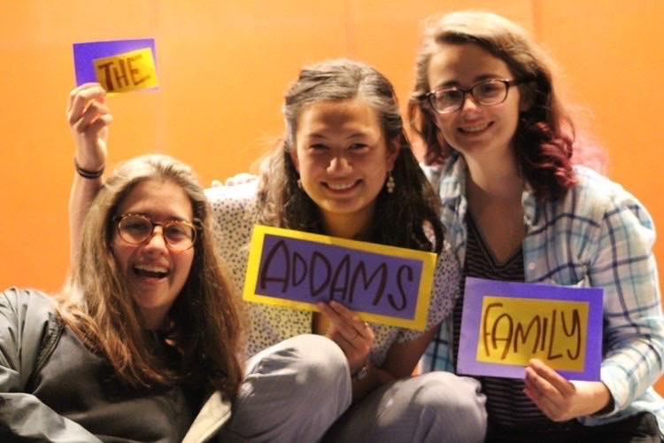 (Left to right) Juniors Daniela Walbridge, Juna Saito, and senior Bridget Lawson hold up signs to promote the Huron Players' next show