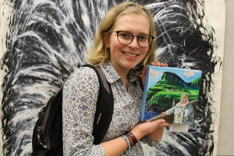 Junior Sophie Larsen holding up her painting which was displayed at Art Night.