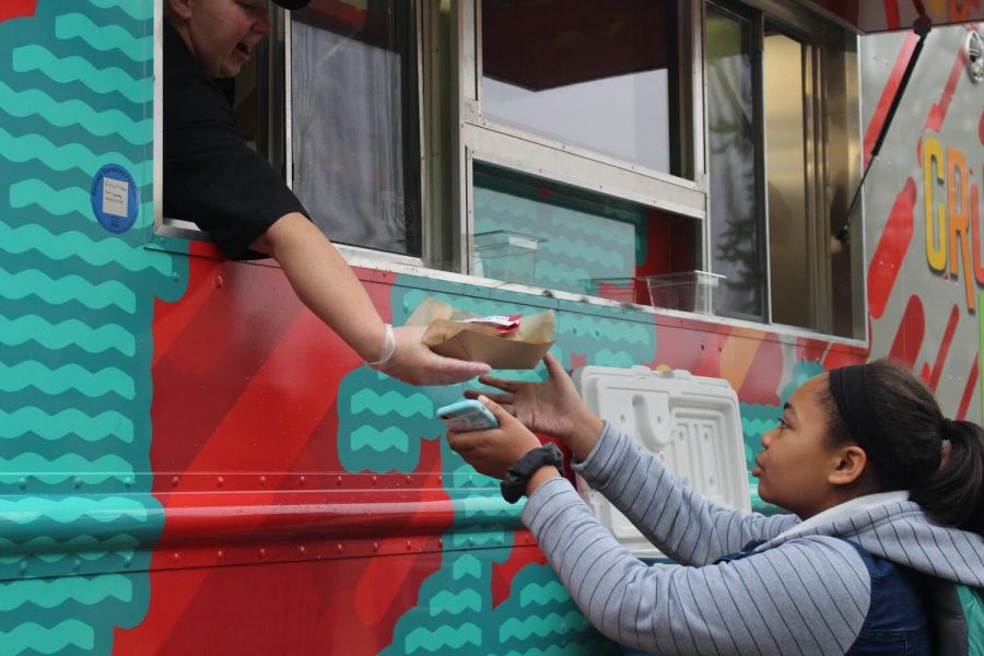 A energetic Chartwell's employee hands an eager student their freshly made steak taco. Students from both early and late lunch stood in long lines to try the highly anticipated dish.