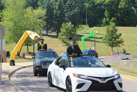 Perked above the sunroof, seniors Alex Cole and Matt Wyderko go through the drive-thru with inflatable props in the background.