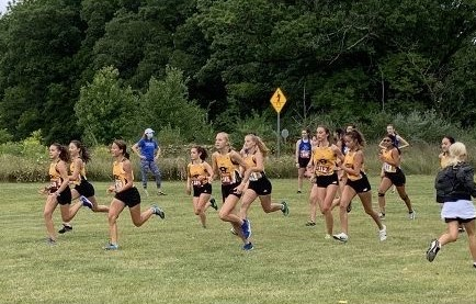 Cross country's women's team warms up for the race with short sprints.