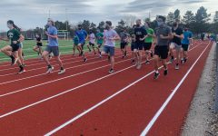 On the opening day of spring sports, track athletes warm up for practice.