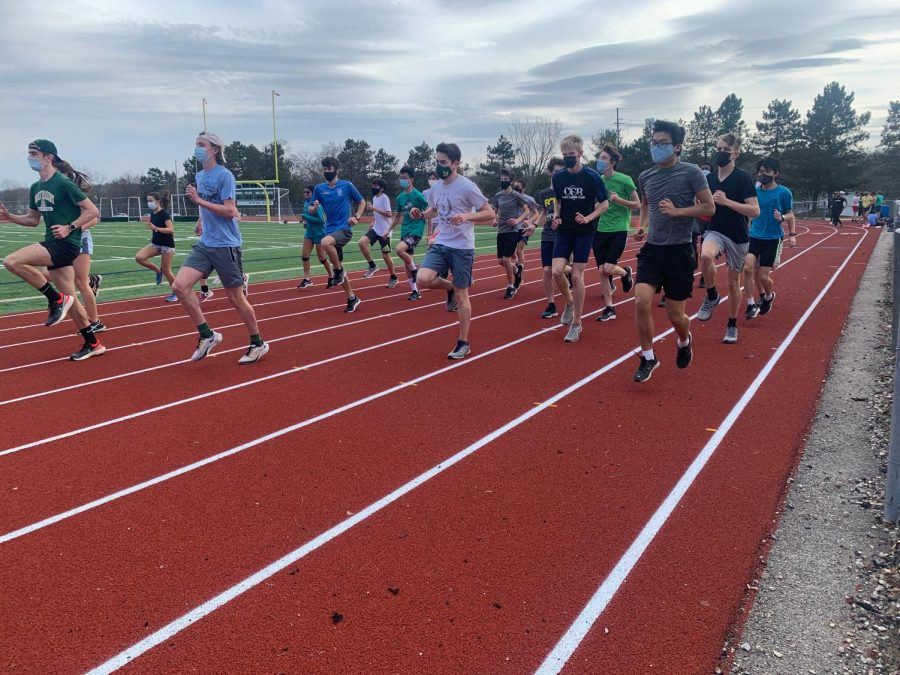 On+the+opening+day+of+spring+sports%2C+track+athletes+warm+up+for+practice.