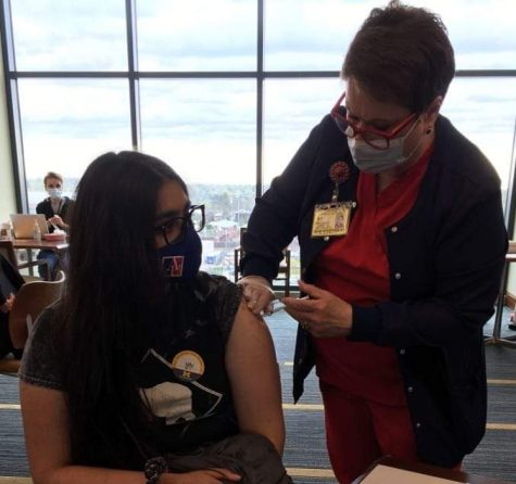 """Senior Mishal Charania receiving the first dose of the Pfizer Bio-NTech vaccine at the Univeristy of Michigan stadium.  """"I am glad we are able"""