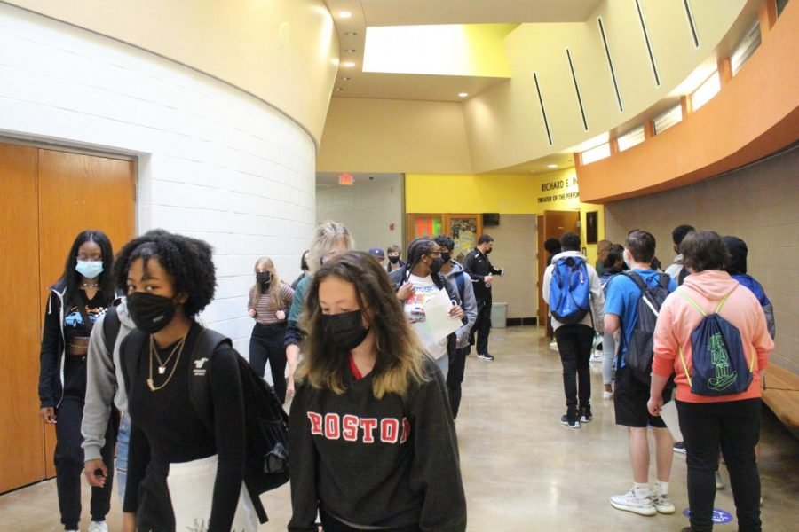 Students walk through the auditorium hallways guided by school social worker Waleed Samaha.