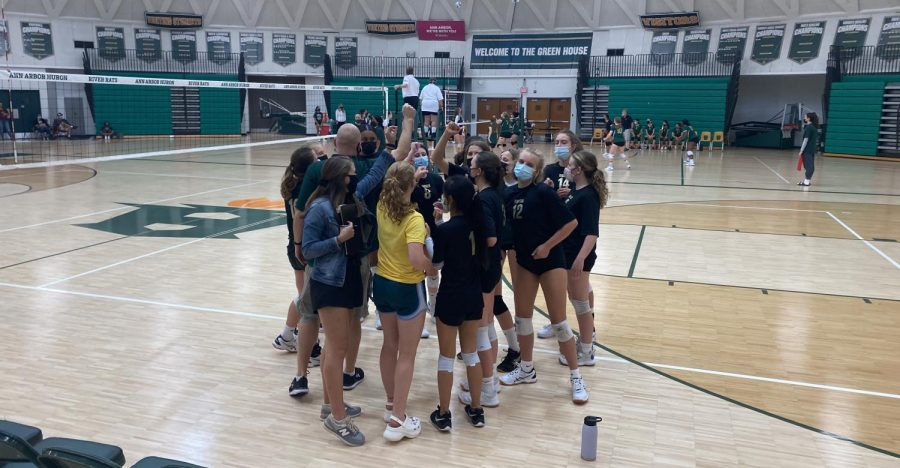 After a quick timeout, the JV volleyball team gathers together on the sideline to cheer before returning to the court.