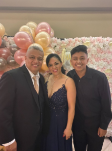 Wilmer Lazo Garcia with his mom and stepdad enjoying a quince they were at.